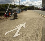 A road marking painting signalling a pedestrian walkway or walki. Ng path on a pier stock photo