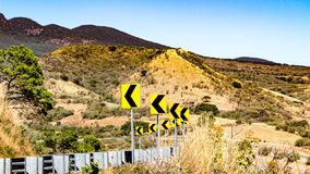 Road marking on the road, dangerous curve with a metal barrier and an arid ground background royalty free stock images