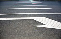 Road markings-with arrows. Closeup of a street with arrows pointing in different directions Royalty Free Stock Images