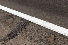 Road markings. In the form of a white strip on the edge of the roadway. Asphalted road with defects. Photo close up Stock Image
