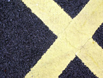 Road Markings in shape of X. Yellow road markings in shape of a cross or X Royalty Free Stock Photo