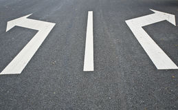 Road markings-with two arrows pointing in opposite directions. Closeup of a street with two arrows pointing in opposite directions Royalty Free Stock Photo