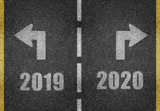 Road markings for the new year. Road markings in white on a black asphalt background saying 2019 with an arrow to the left, and next to it 2020 with an arrow to stock illustration