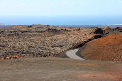 Road in martian landscape of solidified lava in National Park of Timanfaya, Lanzarote volcanic island.  stock photography