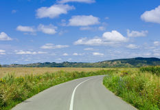 Road and meadow with sky and clouds Royalty Free Stock Photography