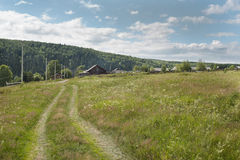 Road in meadow with wild herbs and village Stock Images