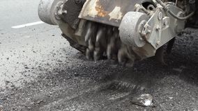 Road milling machine cuts the old asphalt. Road repair. Destruction of the road surface. The cutter cuts a layer of asphalt.  Piec. Es of stone fly apart. Close stock video footage