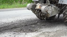 Road milling machine cuts the old asphalt. Road repair. Destruction of the road surface. The cutter cuts a layer of asphalt. Slow. Motion. Pieces of stone fly stock footage
