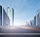 Road in modern city. City road  with blue sky and green fence Royalty Free Stock Image