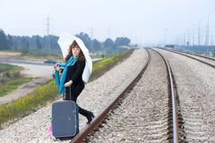 Road Mood. Young woman with a suitcase and umbrella on the railroad. Ready to leave stock photo