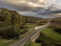 Road on the Moors. A deserted road on the north Yorkshire moors with a stone bridge in the foreground and trees and a stormy sky in the background royalty free stock photography