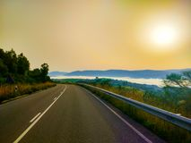 Road at the morning, with mountains over clouds and sunrise at t stock photo