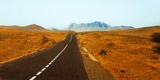 Road in the Moroccan desert. Road without cars in the Moroccan desert under sunset stock photography