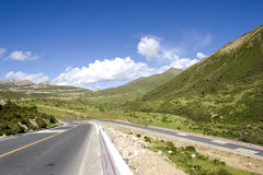 Road in a mountain. Against blue sky and white cloud Royalty Free Stock Image