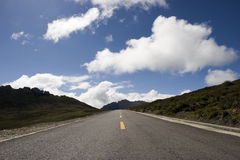 Road in a mountain. Against blue sky and white cloud Stock Photos
