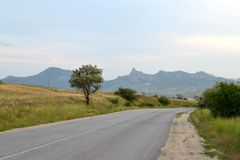 Road, mountain, grass, sky. Road, mountain, grass, the sky, the road goes to the mountains Stock Photo