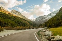 Road through the mountain pass. Curving tarmac road with white continuous line markings leading through a pass between (snowy) mountain peaks and with fir tree stock image