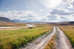 Road on a mountain plateau with the green grass at the background of the valley of white river Royalty Free Stock Images