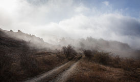 Road between the mountain slopes in the fog Royalty Free Stock Photography