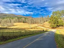 Road Through a Mountain Valley. Scenic rural road with pasture, mountains, and clouds, on a peaceful winter morning. Shadows give it a secluded feeling royalty free stock photos