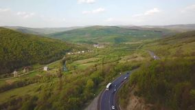 Road in mountain village. Aerial Panorama of Carpathian valley. Highway in mountains. Evening sunlight on hills. Beskid range of Carpathian mountains, Ukraine stock video footage