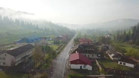 Road in mountain village. Aerial Panorama of Carpathian valley. Road in mountain village. Rural spring misty landscape. Aerial Panorama of Carpathian valley stock video