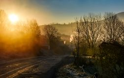 Road through mountain village at foggy sunrise. Beautiful rural scenery in autumn Stock Photos