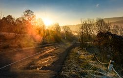 Road through mountain village at foggy sunrise. Beautiful rural scenery in autumn Royalty Free Stock Photo