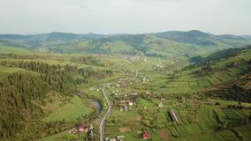 Road in mountain village. Aerial Panorama of Carpathian valley. Road in mountain village. Rural spring misty landscape. Aerial Panorama of Carpathian valley stock video footage