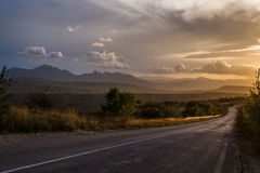 The road in the mountains. Clouds in the sunset. Stock Photo