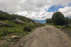 Road in mountains. Dirt road in mountains. Cloudy Stock Photos