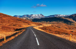 Road in mountains. Fantastic autumn landscape. Bridge over a cha. Nnel connecting Jokulsarlon Lagoon and Atlantic Ocean in southern Iceland Royalty Free Stock Photos
