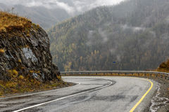 Road mountains fog hairpin curve. Scenic view of the hairpin bend wet winding road through the pass, part of the mountain serpentine in autumn cloudy weather stock photography