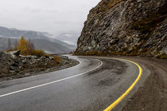 Road mountains fog hairpin curve. Scenic view of the hairpin bend wet winding road through the pass, part of the mountain serpentine in autumn cloudy weather royalty free stock image