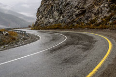 Road mountains fog hairpin curve. Scenic view of the hairpin bend wet winding road through the pass, part of the mountain serpentine in autumn cloudy weather royalty free stock images