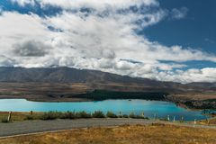 Road in the mountains, Lake Tekapo, and dramatic cloudy sky, North Island New Zealand. Scenic view of Lake Tekapo and mountains, road trip, New Zealand stock images
