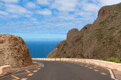 Road between mountains leading to the sea Royalty Free Stock Photos