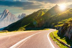 Road in mountains with rocky ridge at sunset royalty free stock image