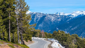 Road in the mountains. Road in the snow mountains with forest Royalty Free Stock Image