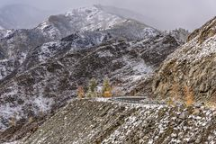 Road mountains snow hairpin curve. Scenic view of the hairpin bend winding road through the pass, part of a mountain serpentine, in the autumn cloudy weather stock photos