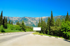 The road in the mountains of spruce and cypress trees. The road disappearing into the distance among the firs and cypresses. Crimean mountains in Ukraine. Space Stock Photos
