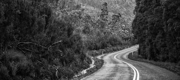 Road and mountains in the Tasmanian countryside. Black and white Stock Photo