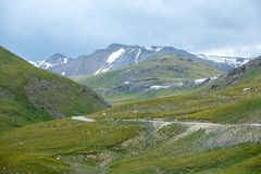 Road in mountains of Tien Shan at cloudy day Stock Photos