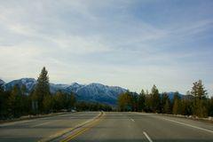 Road, Mountains, and Trees Royalty Free Stock Image