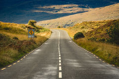 Road in the mountains. Two lane road in the mountais with yellow sign Royalty Free Stock Photo