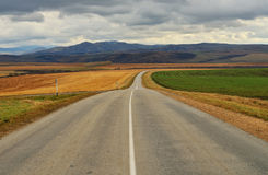 Road in the mountains. Under sky clouds and fields Stock Photography