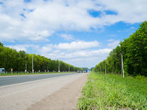 Road with moving cars and green surroundings on the sides Stock Photo