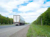 Road with moving cars and green surroundings on the sides Stock Photos