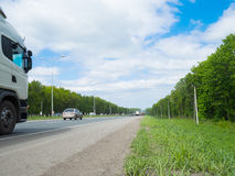 Road with moving cars and green surroundings on the sides Royalty Free Stock Image