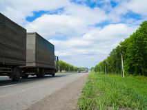Road with moving cars and green surroundings on the sides Royalty Free Stock Photo